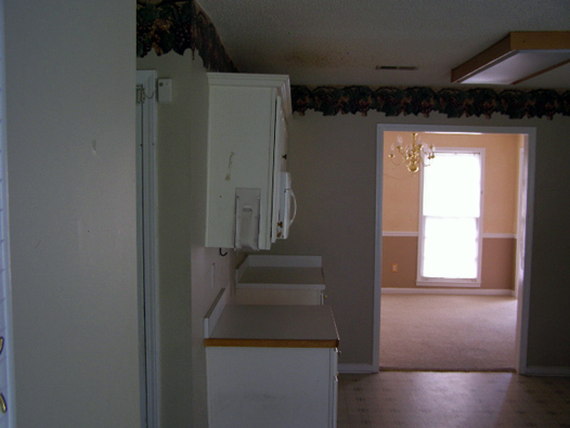 Kitchen Before: Border, White Laminate Cabinets, Vinyl Floors 3