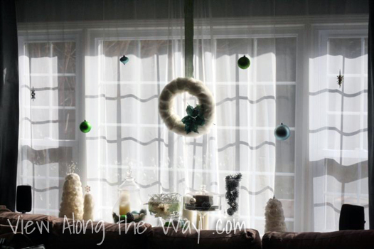 Christmas ornaments hung in a window