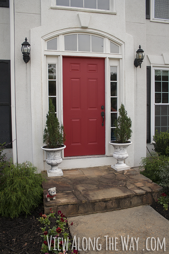 Red Front Door On A Grey House, With Spruce Trees